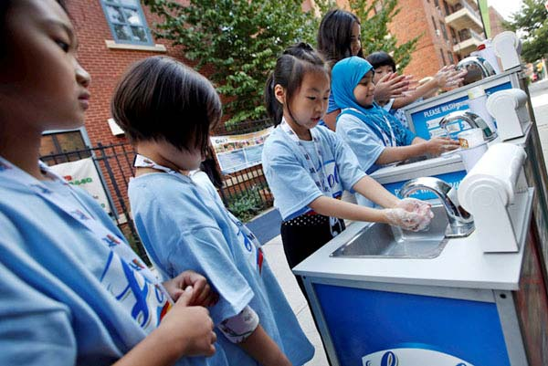 Better Society: children gathered at hand-washing stations learning about cleanliness and hygiene habits.